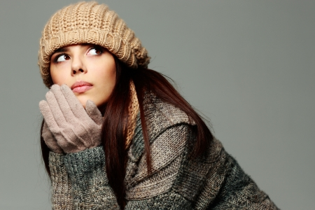 Young pensive woman in warm winter outfit looking away photo