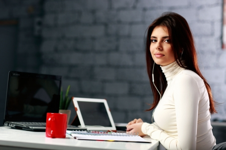 Young businesswoman sitting at the table on her workplace in office photo