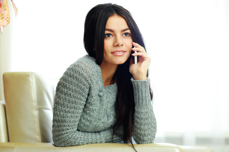Young pensive woman talking on the phone at home photo