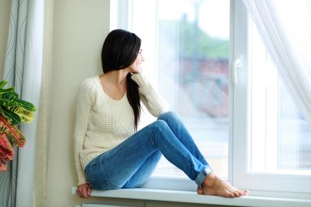 窓の土台の上に座って、外を見て若いの幸せな女