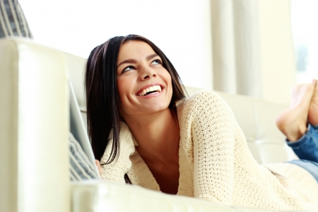 Young laughing woman lying on the sofa and looking up at home photo