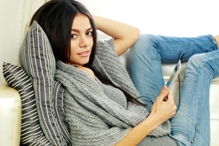 Thoughtful young woman resting on a sofa with tablet computer at home photo