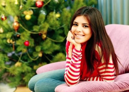 Young smiling woman sitting on the sofa at home photo