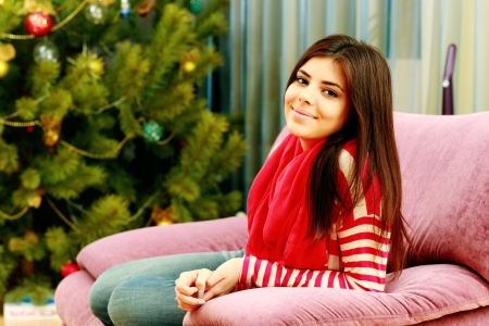 Young happy woman sitting on the sofa at home photo