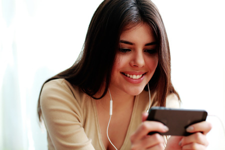Young happy smiling student using smartphone isolated on a white background photo