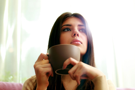 pensive woman: Young pensive woman with cup of coffee looking away Stock Photo