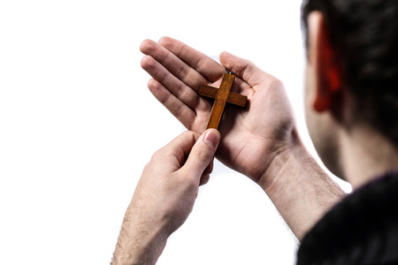 Male hands holding wooden cross on white background photo