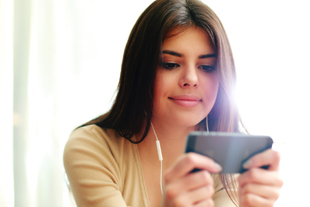 Young happy female student using smartphone at home photo
