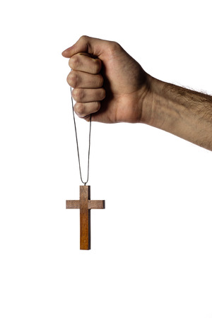 Male hand holding wooden cross on white background photo