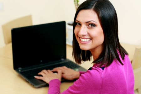 Young happy woman typing on the laptop and looking at camera photo