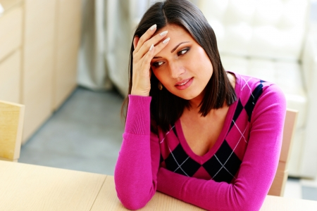 Young pensive woman sitting at the table at home Stock Photo - 25336238
