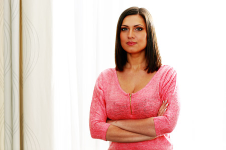 Portrait of a young beautiful woman with arms folded photo