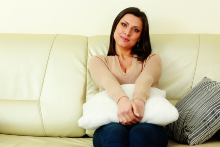 Portrait of a young happy woman sitting on the sofa photo