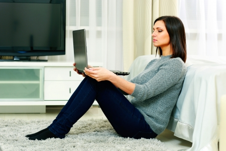 middle-aged beautiful woman sitting on the floor and using laptop at home photo
