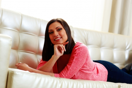 Young happy smiling woman lying on the sofa photo