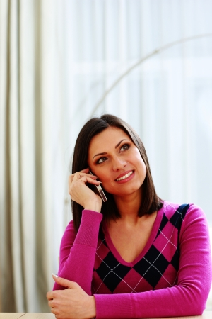 Middle-aged smiling woman talking on the phone and looking away photo
