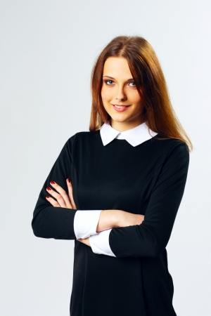 Young cheerful woman standing with arms folded on gray background  photo