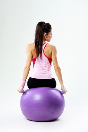 Back view of a young sport woman sitting on fitball with dumbells on gray background photo