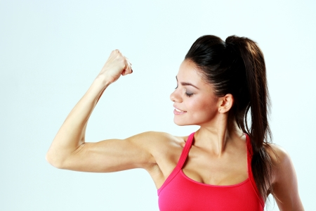 Young sport woman looking at her biceps on gray bakground photo