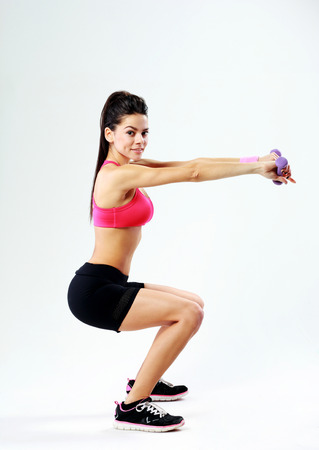 Young happy sport woman doing squats with dumbbells on gray  photo