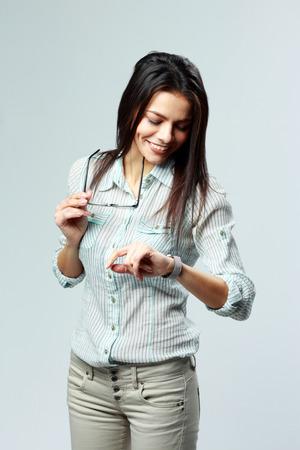 punctual: Joven alegre mujer de negocios mirando su reloj en la muñeca en fondo gris Foto de archivo