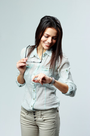 punctual: Young cheerful businesswoman looking at her watch on wrist on gray background