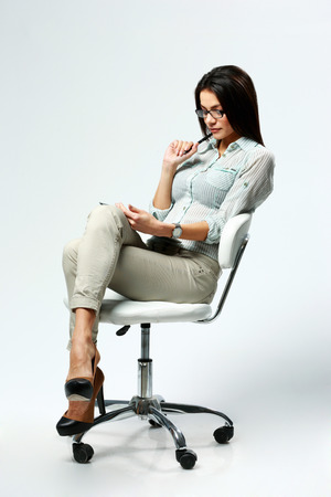 swivel: Young beautiful woman sitting on the chair and using table computer on gray background