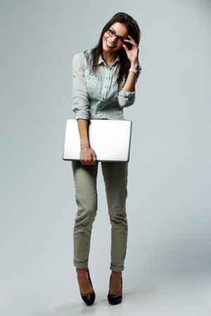 Full-length portrait of a young smiling businesswoman holding laptop on gray  photo
