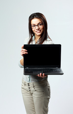 Young happy businesswoman showing laptop on gray  photo