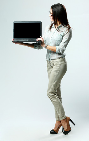 Young businesswoman looking on a laptop on gray  photo