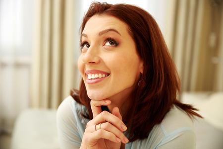 femme regarde en haut: Smiling woman looking up at home