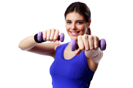 Young happy sport woman with dumbbells working out isolated on white background. Focus on dumbbells photo