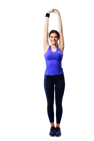 Full-length portrait of a smiling sport woman stretching hands isolated on white background photo