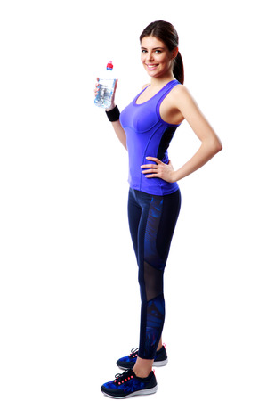 Full-length portrait of a smiling sport woman holding bottle with water isolated on white background photo