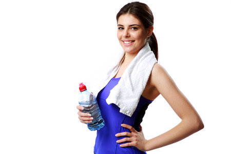Young cheerful sport woman holding bottle with water isolated on white background photo