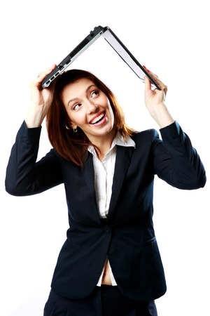 Laughing businesswoman holding a laptop above her head like a roof isolated on a white background photo