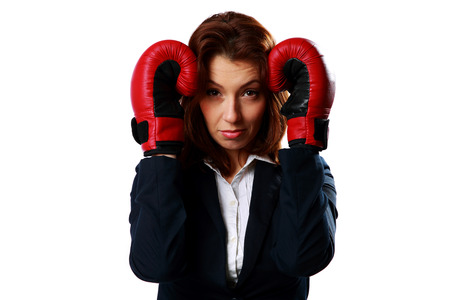 Businesswoman wearing boxing gloves standing in protective pose, isolated on a white background photo