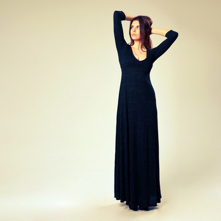 Young beautiful woman in long dress looking away on gray background photo