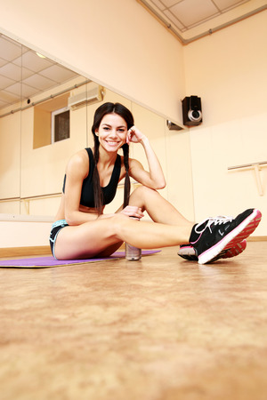 Young happy fit woman sitting on the floor at gym photo