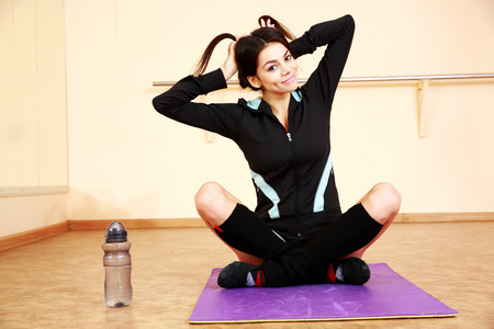 Young funny fit woman sitting on the yoga mat at gym photo