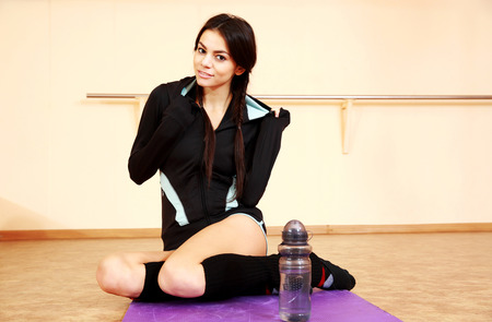 Young happy fit woman resting on yoga mat at gym Stock Photo - 26554609