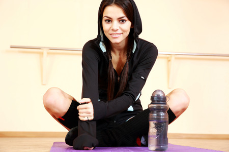 Young smiling fit woman sitting on the yoga mat at gym photo