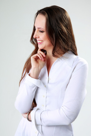 Smiling woman standing and looking away on gray background photo