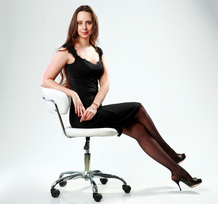 Beautiful woman in black dress sitting on the office chair over gray background photo