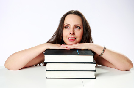 Thoughtful woman sitting on the table with books over gray background photo