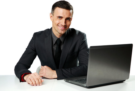 Cheerful businessman sitting at the table with laptop isolated on a white background Stock Photo