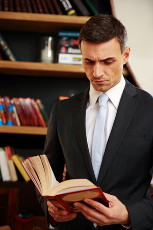 concetrated: Businessman reading the book in library