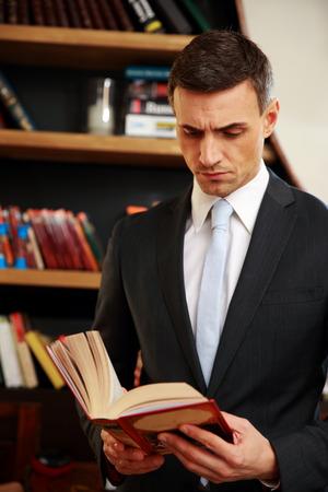 director de escuela: Empresario leyendo el libro en la biblioteca
