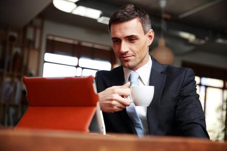 empresario: Empresario beber caf� y leyendo las noticias en la cafeter�a Foto de archivo