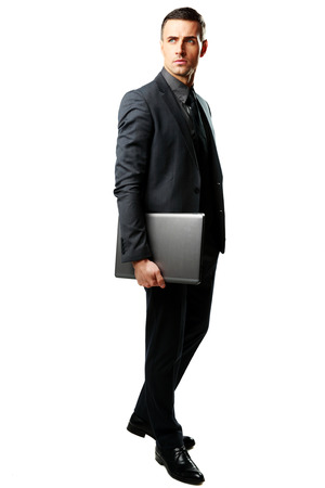 Full-length portrait of a businessman standing with laptop isolated on a white background photo